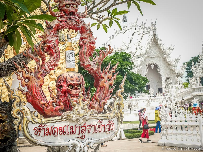 "A sign with a red skull stating that ""alcohol is a sin"" at White Temple (Wat Rong Khun) in Chiang-Rai"